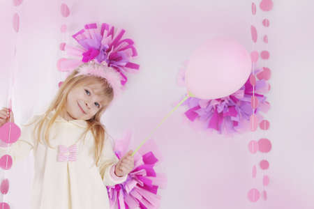 Happy little girl at pink decorated birthday party with balloon photo