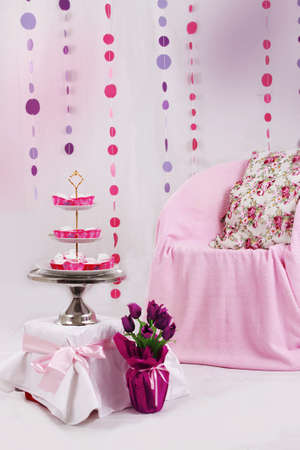 Pink baby shower decor with garland and dessert table photo