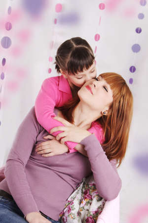 Mother and daughter kissing, pink decoration photo