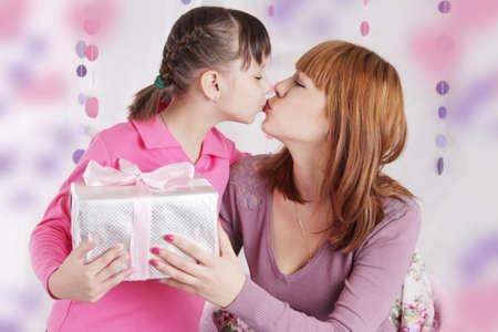 jeune fille adolescente: Mère et fille embrassant et tenant présents, décoration rose Banque d'images