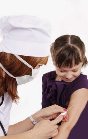 intramuscular: Woman doctor vaccinating girl in hand over white
