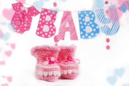 Pink bootees and baby word garland as decoration photo