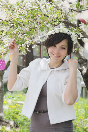 Happy woman with wreath among spring garden photo
