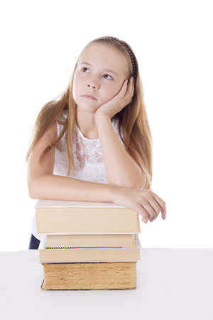 Thoughtful schoolgirl with pile of books isolated on white photo