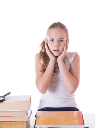 Horrified schoolgirl with pile of books isolated on white photo
