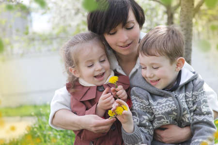 Happy mother and two children admiring spring garden