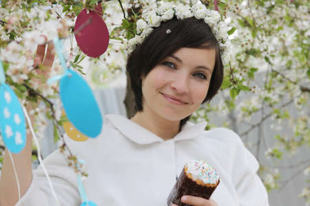 Sensual woman with wreath and Easter cake among spring garden photo