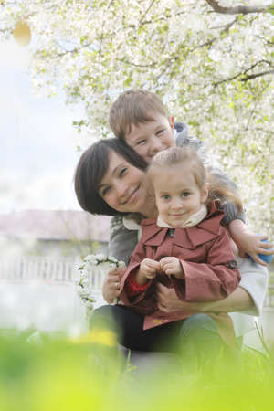 Happy mother and two children hugging among blooming garden Stock Photo - 28080960