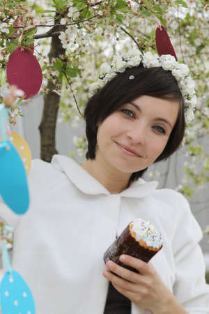 Sensual woman with wreath and Easter cake among spring garden Stock Photo - 28080963