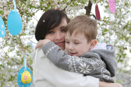 Happy mother and son in blooming garden decorating for Easter Stock Photo - 28080965