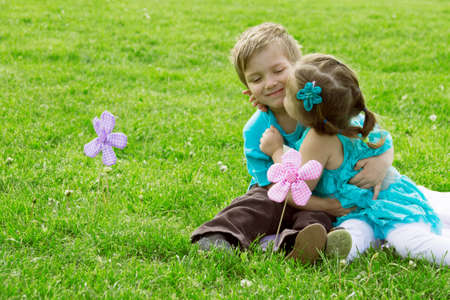 Happy little boy and girl kissing in green grass photo