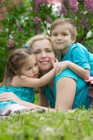 Happy mother and two children hugging among green grass photo