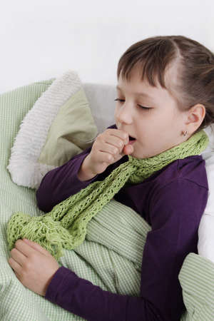 Ill girl coughs lying in bed with scarf Stock Photo