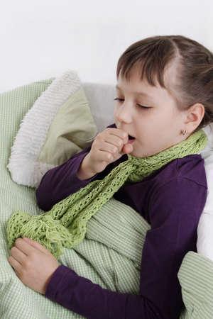 Ziek meisje hoesten liggend in bed met een sjaal