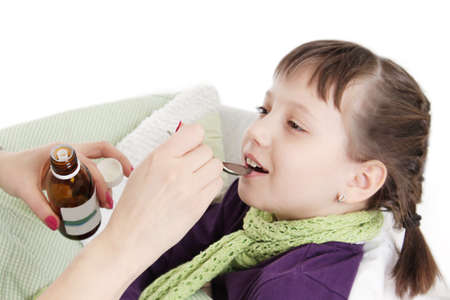 Mothre hand giving spoon dose of medicine liquid drinking syrup to child over white photo