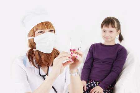 Doctor with syringe needle and girl scared of injections, focus on doctor photo