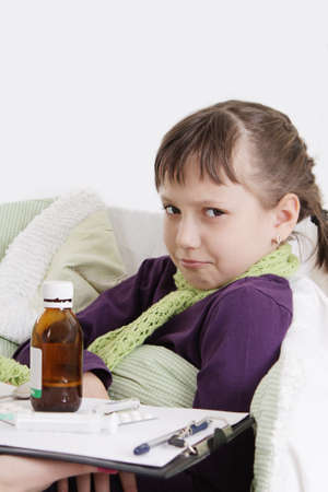 Upset girl lying in bed with medicine photo