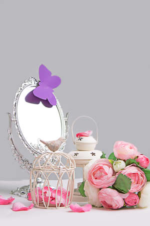 Rustic white decoration of cage, lantern and silver mirror photo