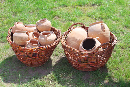 Ancient clay pots in basket over green grass photo