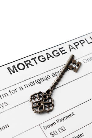 considerations: Silver vintage key against mortgage agreement Stock Photo