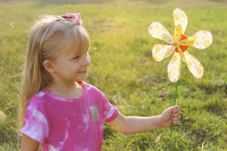 Smiling girl with colorful pinwheel in sunset light photo