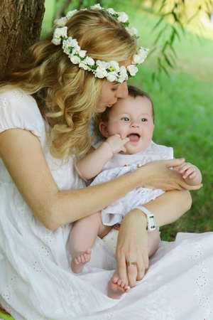 Mother in wreath kissing baby girl outdoor photo