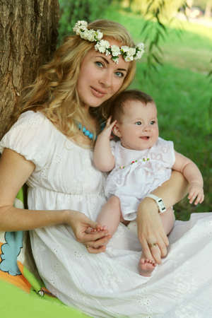 Mother in wreath and baby girl sitting under tree photo