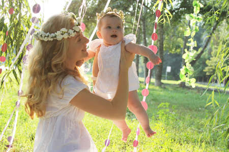 Happy mother and baby girl having fun outdoor on sunny day photo