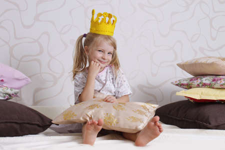 Cute girl in princess crown at pyjamas party photo
