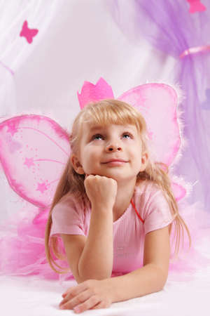 Little princess girl in pink crown and butterfly wings making wishes photo