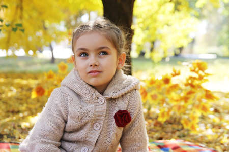 Sad girl looking up under autumn tree photo