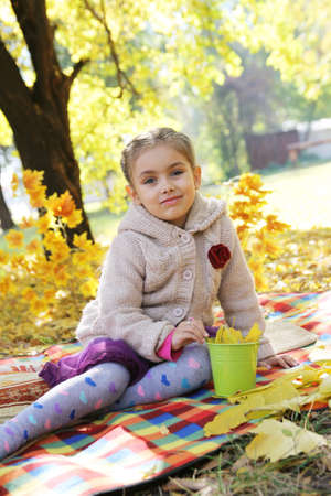 Smiling four year girl sitting under autumn tree photo