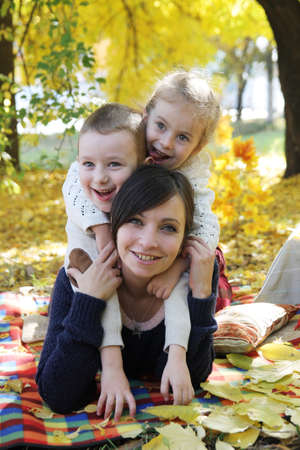 Happy mother and two children lying under autumn trees photo