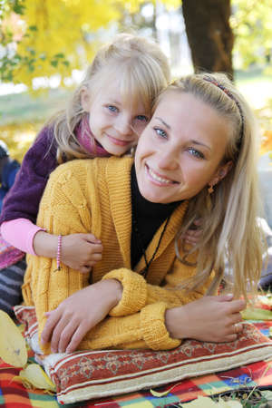 Smiling mother and daughter lying under autumn tree photo