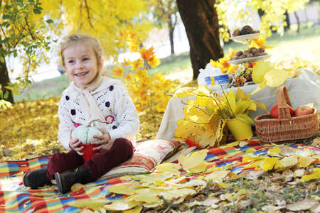 Happy girl holding handmade pumpkin under autumn tree photo