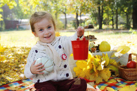 Happy girl showing red busket under autumn trees photo