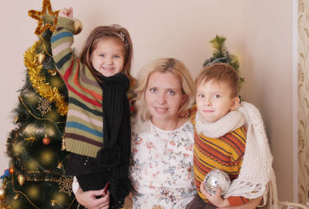 Mother and two children having fun over Christmas tree photo