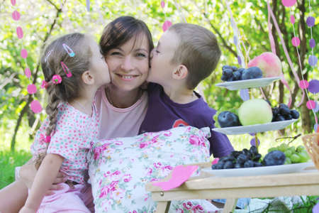 Mother and two chidren kissing at summer picnic photo