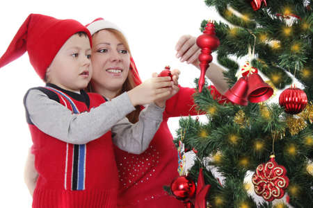 Mother and little boy as Santa helper decorating Christmas tree over white photo