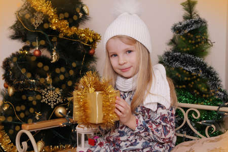 gold facial: Cute girl in knitted hat with Christmas golden gift Stock Photo