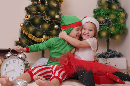 Two children in Christmas costumes having fun with presents photo