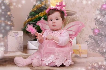 Angel like baby girl with pink butterfly wings sitting under Christmas tree photo