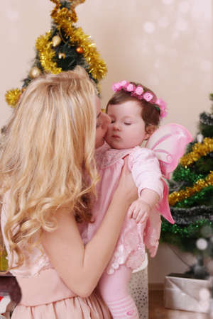 Tender mother kissing her baby girl dressed angel like at Christmas