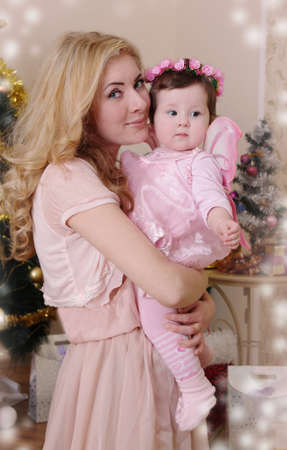 dearly: Mother hugging baby girl dressed like angel
