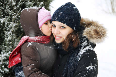 Daughter kissing mother among snowy landscape photo