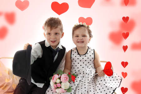 Smiling girl and boy sitting together like lady and gentleman, valentine theme photo