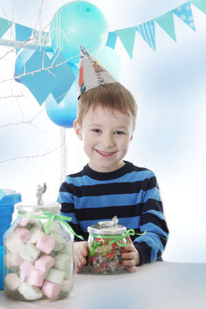 Smiling boy having birthday party in blue decor with sweets photo