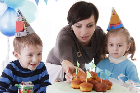 Happy mother and two baby having birthday party in blue decor with cakes photo