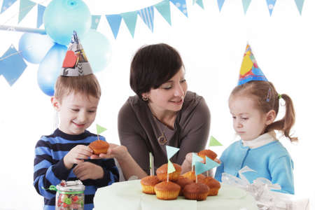 Happy family celebrating birthday party with cakes, blue decor photo