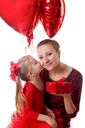 Cute girl kissing mother and giving gift box with balloons over white photo